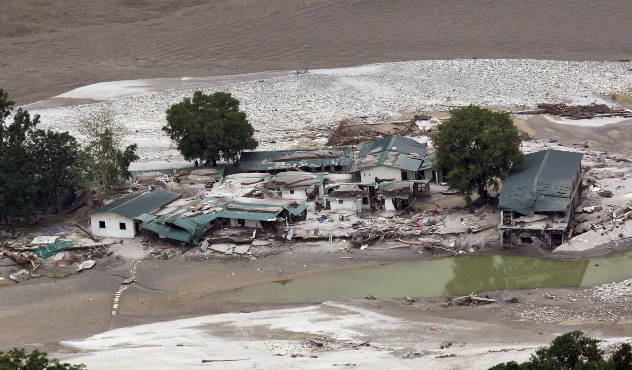 Damaged houses are seen by River Ganges in Guptkashi, India, Sunday, June 23, 2013 photo. The unprecedented heavy rains triggered landslides and floods in the Ganges River last week, washing away thousands of houses and roads and cutting communication links in large areas of Uttarakhand. Soldiers recovered more bodies as they cleared debris in villages bringing the death toll above 1,000, the home minister said Monday. (AP Photo)