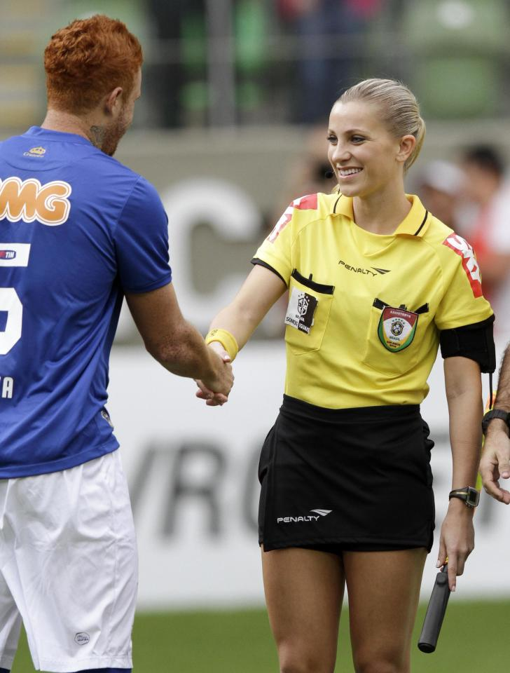 Brazil's referee assistant Fernanda Colombo Uliana is greeted by Cruzeiro's Souza before the Brazilian championship soccer match between Atletico Mineiro and Cruzeiro in Belo Horizonte May 11, 2014. Uliana has just been granted FIFA official status by the refereeing committee of the Brazilian Football Confederation. REUTERS/Washington Alves (BRAZIL - Tags: SPORT SOCCER)