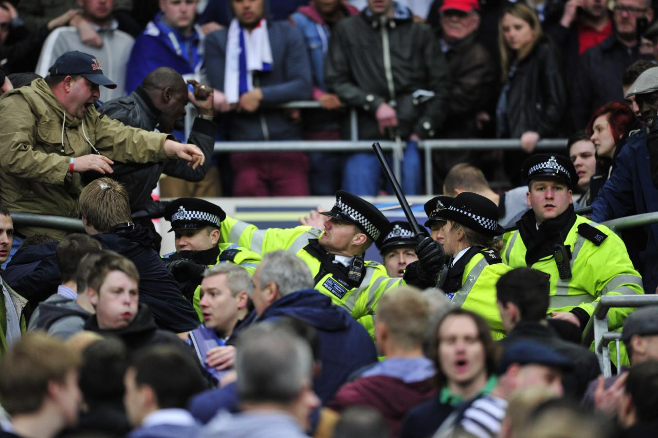 Millwall fans clash with police in the crowd during the FA Cup semi-final football match between Millwall and Wigan Athletic at Wembley Stadium in north London on April 13, 2013. Wigan won the game 2-0. AFP PHOTO/GLYN KIRK  NOT FOR MARKETING OR ADVERTISING USE / RESTRICTED TO EDITORIAL USEGLYN KIRK,GLYN KIRK/AFP/Getty Images