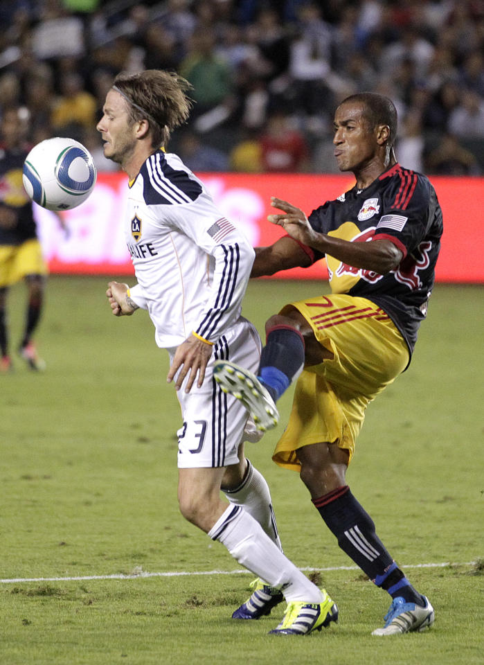 Los Angeles Galaxy midfielder David Beckham, left, of England, is fouled by New York Red Bulls defender Roy Miller during the second half of the second game of an MLS soccer Western Conference semifinal at Home Depot Center in Carson, Calif., Thursday, Nov. 3, 2011. The Galaxy won 2-1. (AP Photo/Jae Hong)