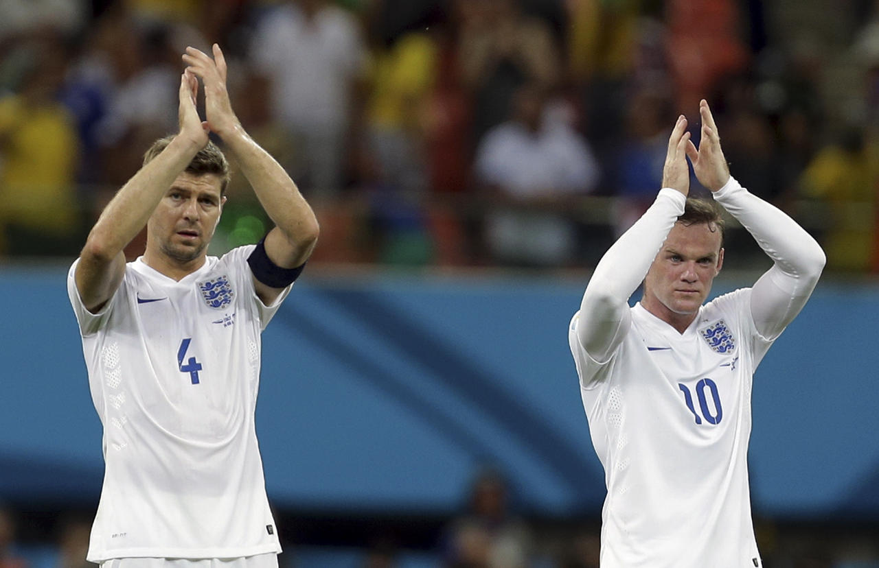 England's Steven Gerrard, left, and Wayne Rooney applaud spectators after the group D World Cup soccer match between England and Italy at the Arena da Amazonia in Manaus, Brazil, Saturday, June 14, 2014. Italy won the match 2-1. (AP Photo/Martin Mejia)