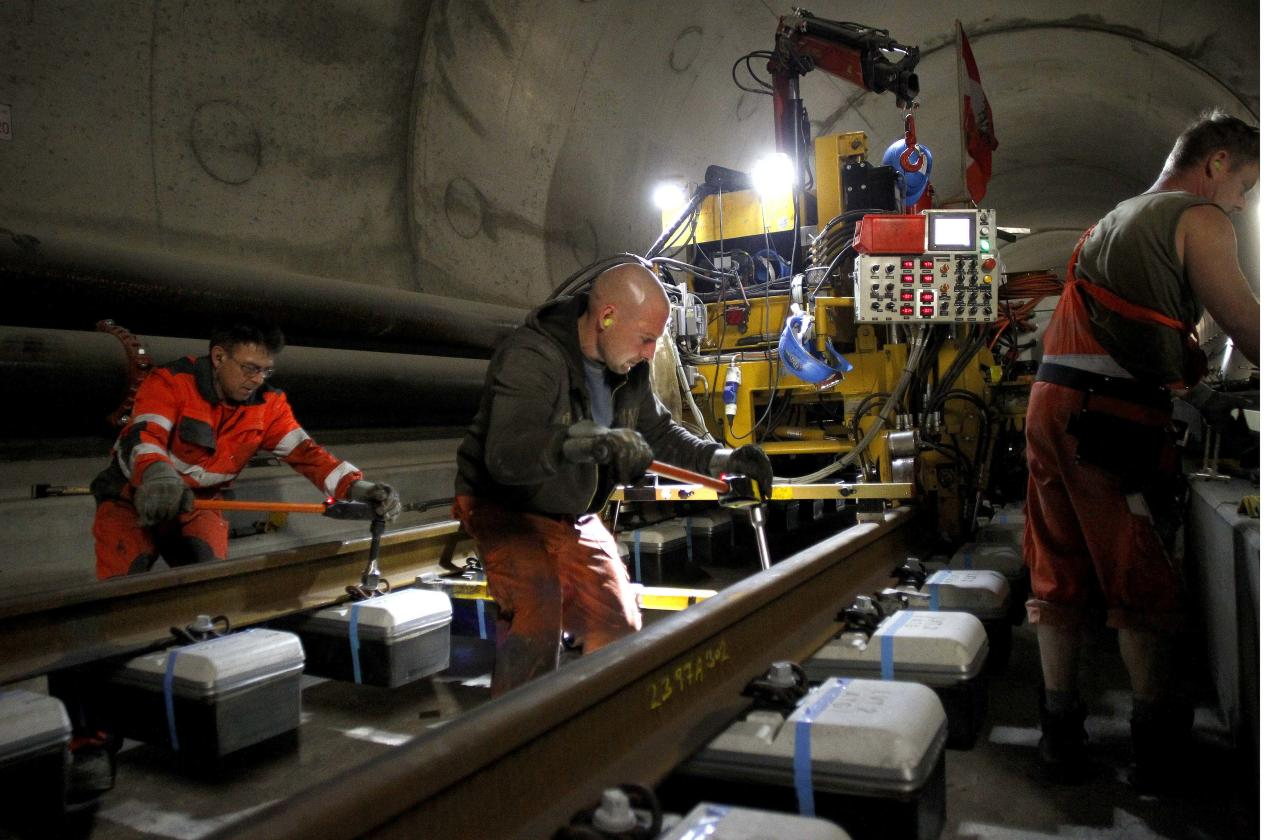 Workers use torque wrenches to fix screw nuts during the installation of the railway tracks in the NEAT Gotthard Base tunnel near Erstfeld May 7, 2012. Crossing the Alps, the world's longest train tunnel should become operational at the end of 2016. The project consists of two parallel single track tunnels, each of a length of 57 km (35 miles) REUTERS/Arnd Wiegmann   (SWITZERLAND - Tags: BUSINESS CONSTRUCTION EMPLOYMENT TRAVEL)