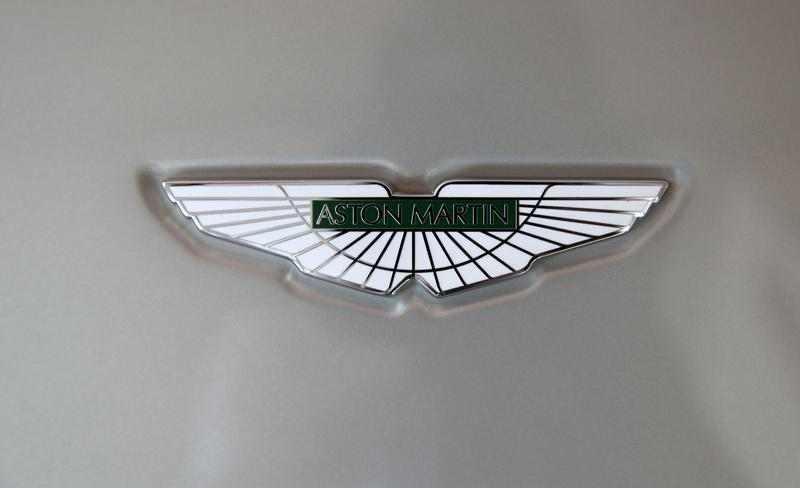 An Aston Martin logo is seen on a car inside the company's showroom in Doha