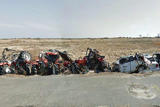 The wreckage of tractors and other vehicles line a road near Namie's shore.