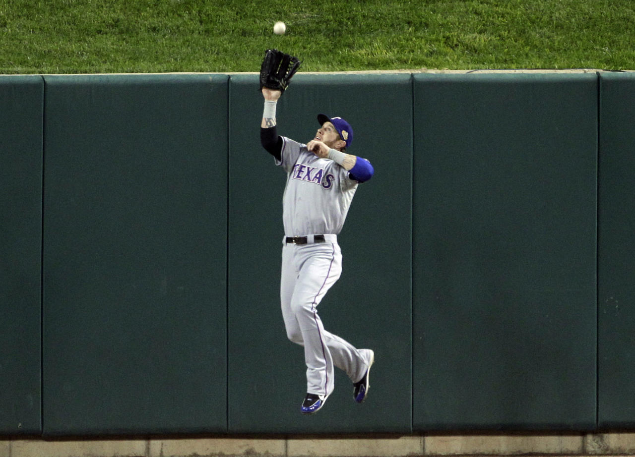 Texas Rangers' Josh Hamilton leaps to catch a fly ball off the bat of St. Louis Cardinals' Yadier Molina during the first inning of Game 7 of baseball's World Series Friday, Oct. 28, 2011, in St. Louis. (AP Photo/Paul Sancya)