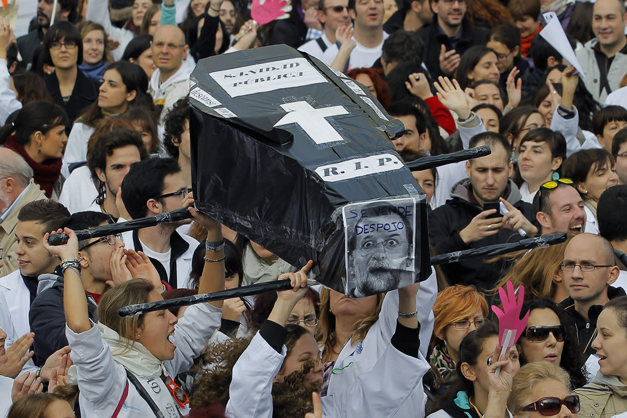 Protestors shout slogans as they hold a coffin representing the health care system during a demonstration against government-imposed austerity measures and labor reforms in the public health care sector in Madrid.