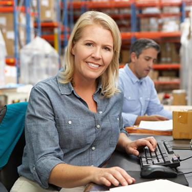 Businesswoman-working-at-desk-at-warehouse_web