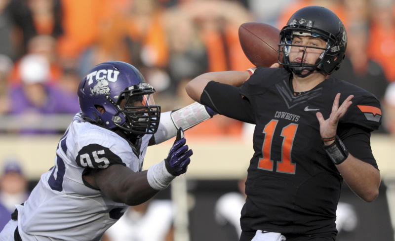 In this Oct. 27, 2012, file photo, TCU defensive end Devonte Fields, left, pressures Oklahoma State quarterback Wes Lunt, right, during an NCAA college football game in Stillwater, Okla. Field as selected as the AP's Big 12 defensive player of the year, Wednesday, Dec. 5, 2012