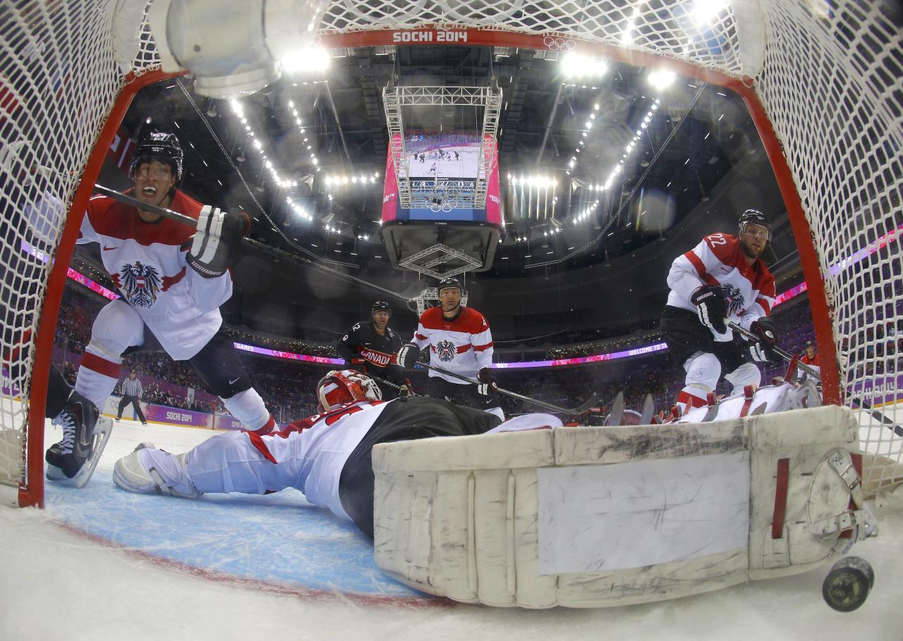 Canada's Jeff Carter (not shown) scores on Austria's goalie Bernhard Starkbaum during the second period of their men's preliminary round ice hockey game at the 2014 Sochi Winter Olympic Games, February 14, 2014. REUTERS/Mark Blich/Pool (RUSSIA - Tags: OLYMPICS SPORT ICE HOCKEY)