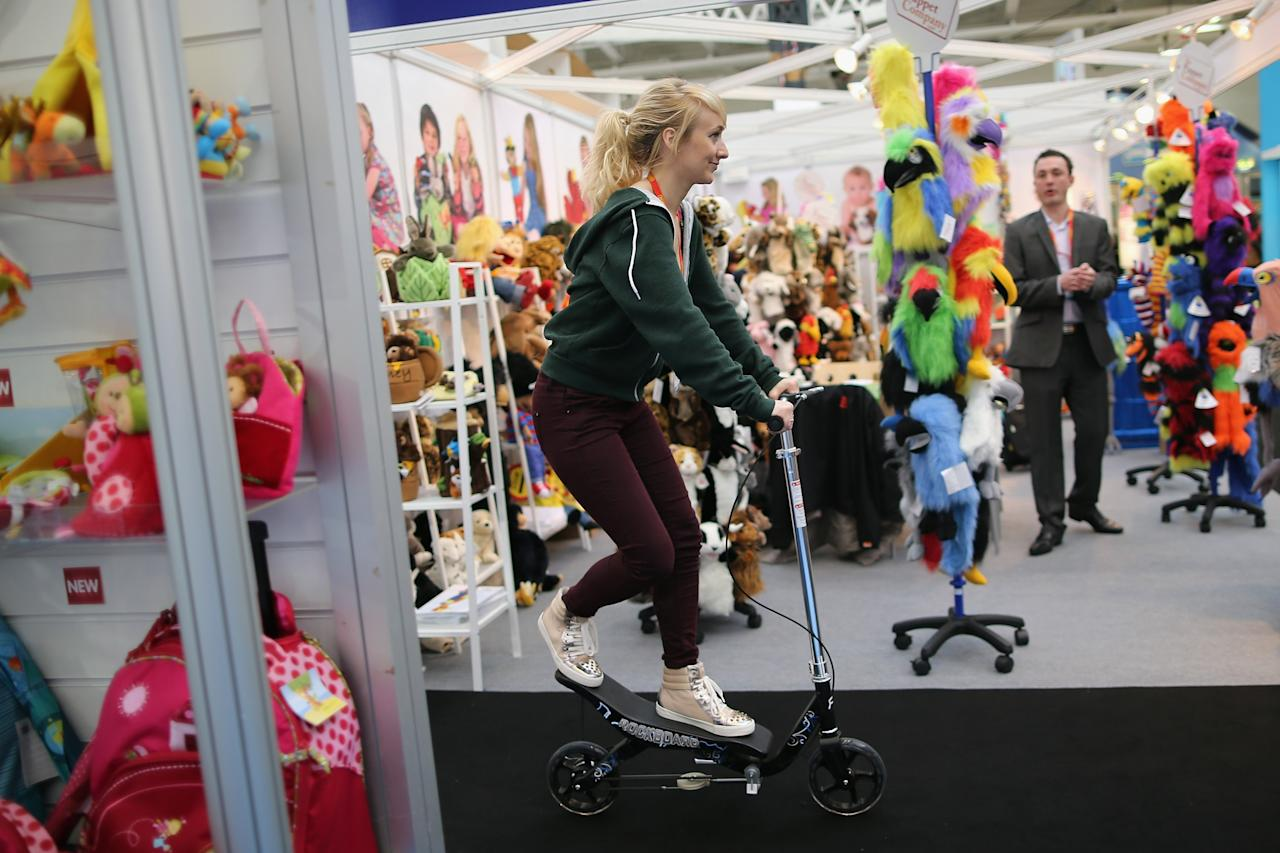 LONDON, ENGLAND - JANUARY 22:  A woman rides a scooter through trade stands during the 2013 London Toy Fair at Olympia Exhibition Centre on January 22, 2013 in London, England. The annual fair which is organised by the British Toy and Hobby Association, brings together toy manufacturers and retailers from around the world.  (Photo by Dan Kitwood/Getty Images)