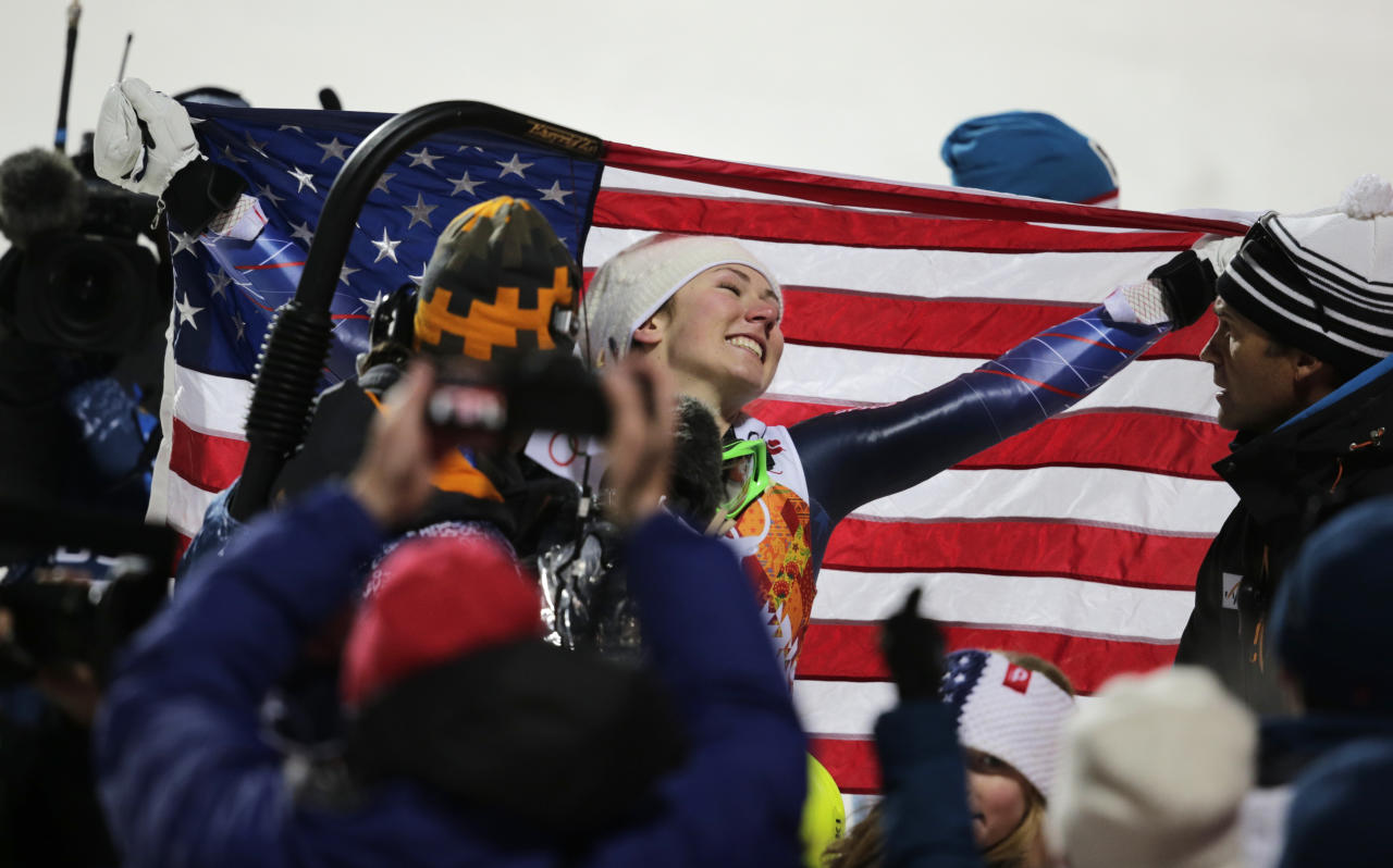 United States' Mikaela Shiffrin poses with the American flag after winning the gold medal in the women's slalom at the Sochi 2014 Winter Olympics, Friday, Feb. 21, 2014, in Krasnaya Polyana, Russia. (AP Photo/Charles Krupa)