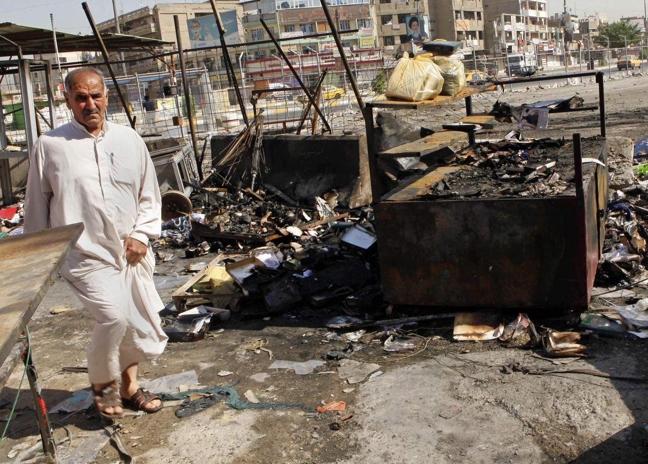 A man inspects the aftermath of a car bomb attack on a store in the New Baghdad neighborhood of Baghdad, Iraq, Sunday, Aug. 11, 2013. A wave of car bombings targeting those celebrating the end of Ramadan across Iraq killed scores of people Saturday, a bloody reminder of the inability of Iraqi authorities to stop violence threatening to spiral out of control. (AP Photo/Hadi Mizban)