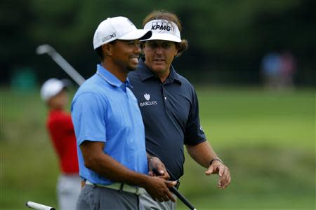 Tiger Woods and Phil Mickelson, both of the United States, walk up the sixth fairway during the first round of the Deutsche Bank Championship golf tournament in Norton