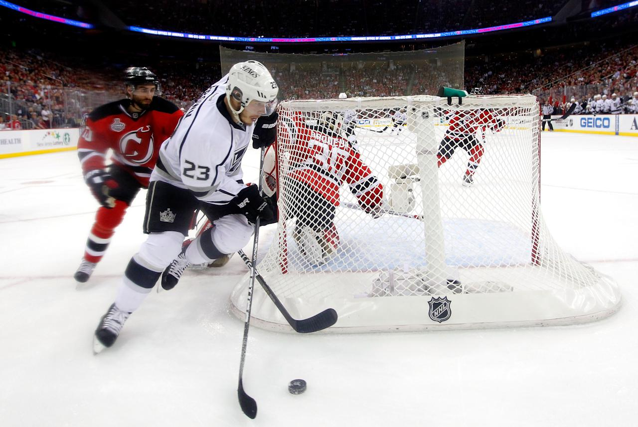 NEWARK, NJ - JUNE 02: Dustin Brown #23 of the Los Angeles Kings handles the puck as Peter Harrold #10 of the New Jersey Devils gives chase during Game Two of the 2012 NHL Stanley Cup Final at the Prudential Center on June 2, 2012 in Newark, New Jersey.  (Photo by Paul Bereswill REMOTE/Getty Images)
