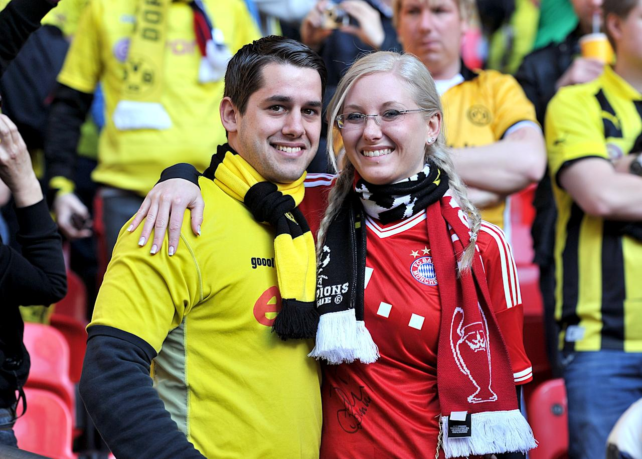 A Borussia Dortmund fan (left) and Bayern Munich fan (right) in the stands before kick-off