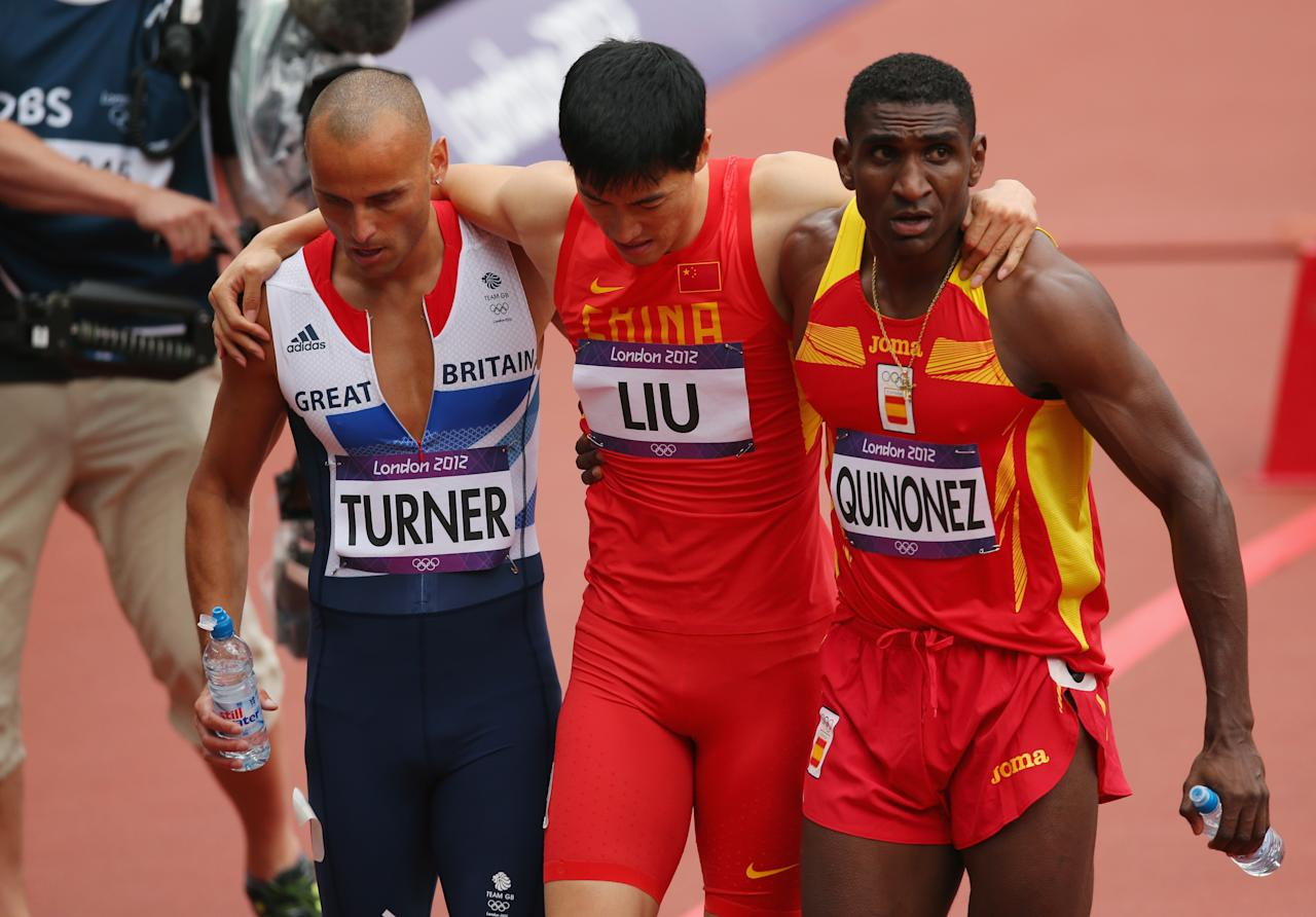 Xiang Liu of China gets assisted off the track by Andrew Turner of Great Britain and Jackson Quinonez of Spain after getting injured in the Men's 110m Hurdles Round 1 Heats on Day 11 of the London 2012 Olympic Games at Olympic Stadium on August 7, 2012 in London, England. (Photo by Cameron Spencer/Getty Images)