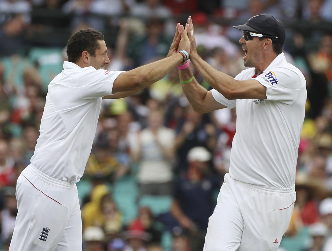 England's Tim Bresnan, left, celebrates with teammate Kevin Pietersen after dismissing Australian captain Michael Clarke on the first day's play of their fifth and final Ashes cricket test at the Sydney Cricket Ground in Sydney, Australia, Monday, Jan. 3, 2011.