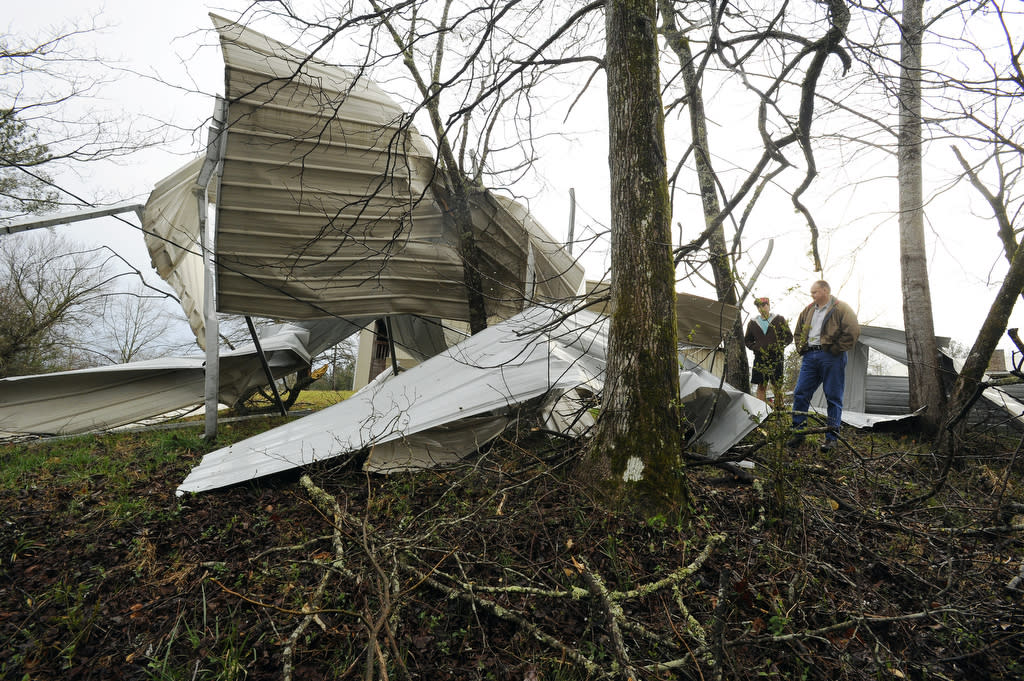 David McCullars, and son David Jr. survey the damage to their 36x48x16 RV shed destroyed by high winds on Ridgetop Lane in Clay, Ala., Monday, March 18, 2013. A severe line of thunderstorms moved through central Alabama just after 3:30 p.m. snapping trees and knocking out power making travel hazardous. Trees fell on power lines that crossed the road on Old Springville Road and Clayton Road. (AP Photo/AL.com, Joe Songer)