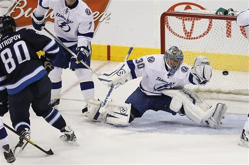 Winnipeg Jets' Nik Antropov (80) scores on Tampa Bay Lightning's goaltender Dwayne Roloson (30) during second-period NHL hockey game action in Winnipeg, Manitoba, Saturday, April 7, 2012. (AP Photo/The Canadian Press, John Woods)
