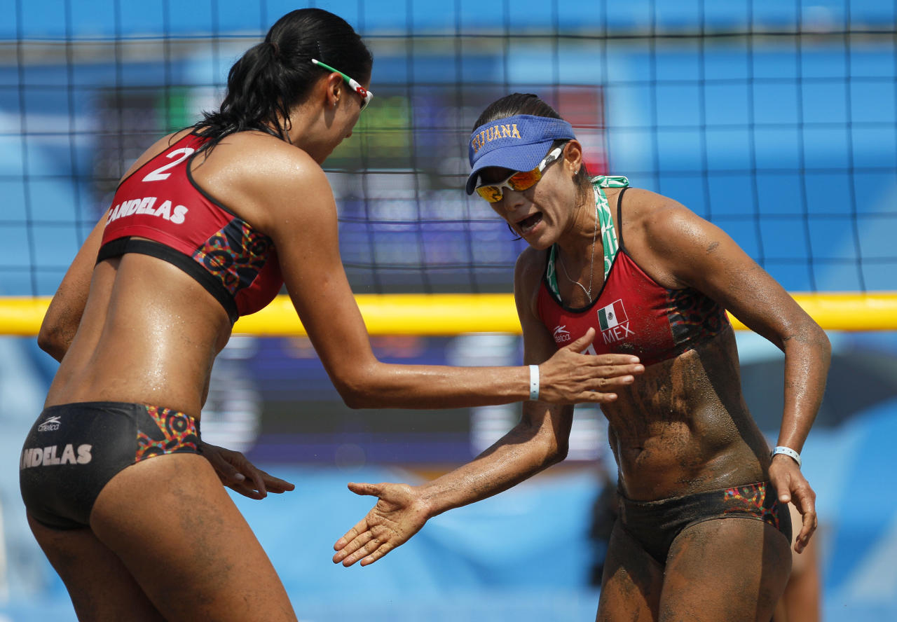 Mexico's Mayra Garcia, right, celebrates a point with teammate Bibiana Candelas during a women's beach volleyball semifinal match against the United States at the Pan American Games in Puerto Vallarta, Mexico, Thursday Oct. 20, 2011. (AP Photo/Ariana Cubillos)