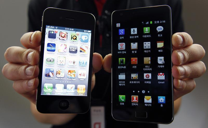 An employee of South Korean mobile carrier KT holds an Apple Inc's iPhone 4 smartphone and a Samsung Electronics' Galaxy S II smartphone as he poses for photographs at a registration desk at KT's headquarters in Seoul