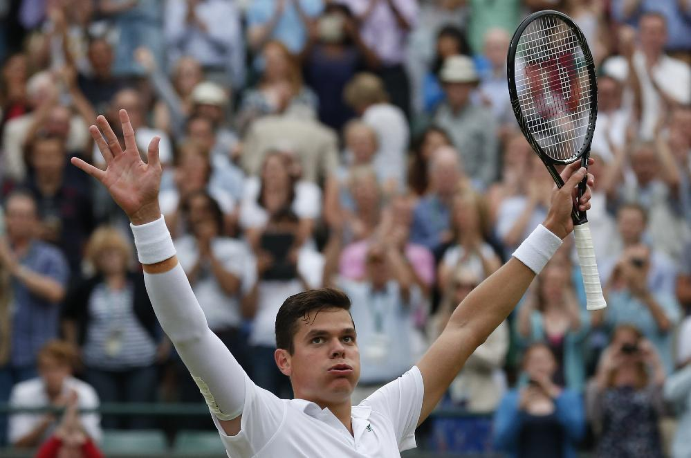 Milos Raonic of Canada puts his arms aloft as he celebrates defeating Nick Kyrgios of Australia in their men's singles quarterfinal match at the All England Lawn Tennis Championships in Wimbledon, London, Wednesday, July 2, 2014. (AP Photo/Ben Curtis)