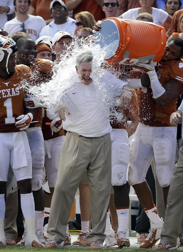 Texas head coach Mack Brown gets dunked by his players after an NCAA college football game against Oklahoma at the Cotton Bowl Saturday, Oct. 12, 2013, in Dallas. Texas won 36-20. (AP Photo/LM Otero)