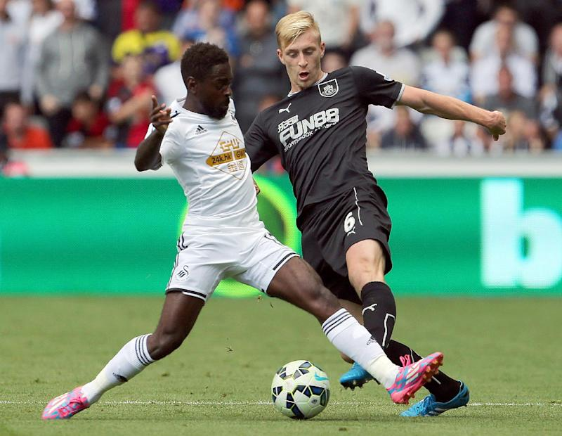 Swansea City's English midfielder Nathan Dyer (L) tackles Burnley's English defender Ben Mee (R) during the English Premier League football match between Swansea City and Burnley at the Liberty Stadium in Swansea on August 23, 2014