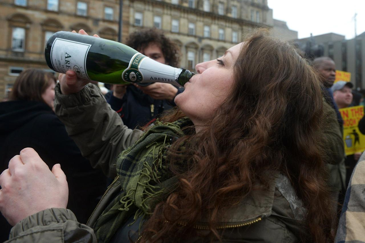 GLASGOW, UNITED KINGDOM - APRIL 08:  A woman drinks cava as members of the public gather in George Square to mark the death of Baroness Margaret Thatcher on April 8, 2013 in Glasgow, Scotland. It has been confirmed that Lady Thatcher has died this morning following a stroke aged 87. Margaret Thatcher was the first female British Prime Minster and governed the UK from 1979  to 1990. She led the UK through some turbulent years and contentious issues including the Falklands War, the miners' strike and the Poll Tax riots.  (Photo by Jeff J Mitchell/Getty Images)