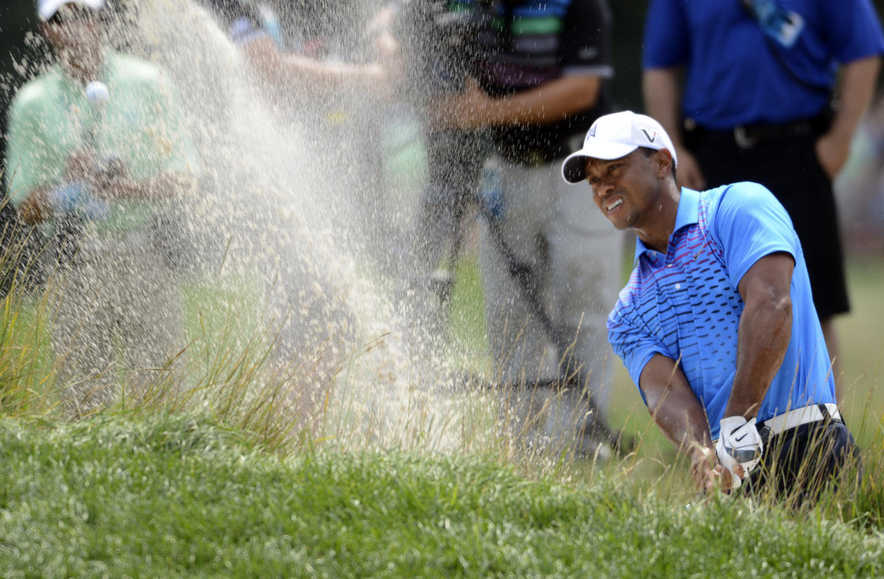 Tiger Woods blasts out of a sand trap on the second hole during the second round of The Barclays golf tournament at Bethpage State Park in Farmingdale, N.Y., Friday, Aug. 24, 2012. (AP Photos/Henny Ray Abrams)