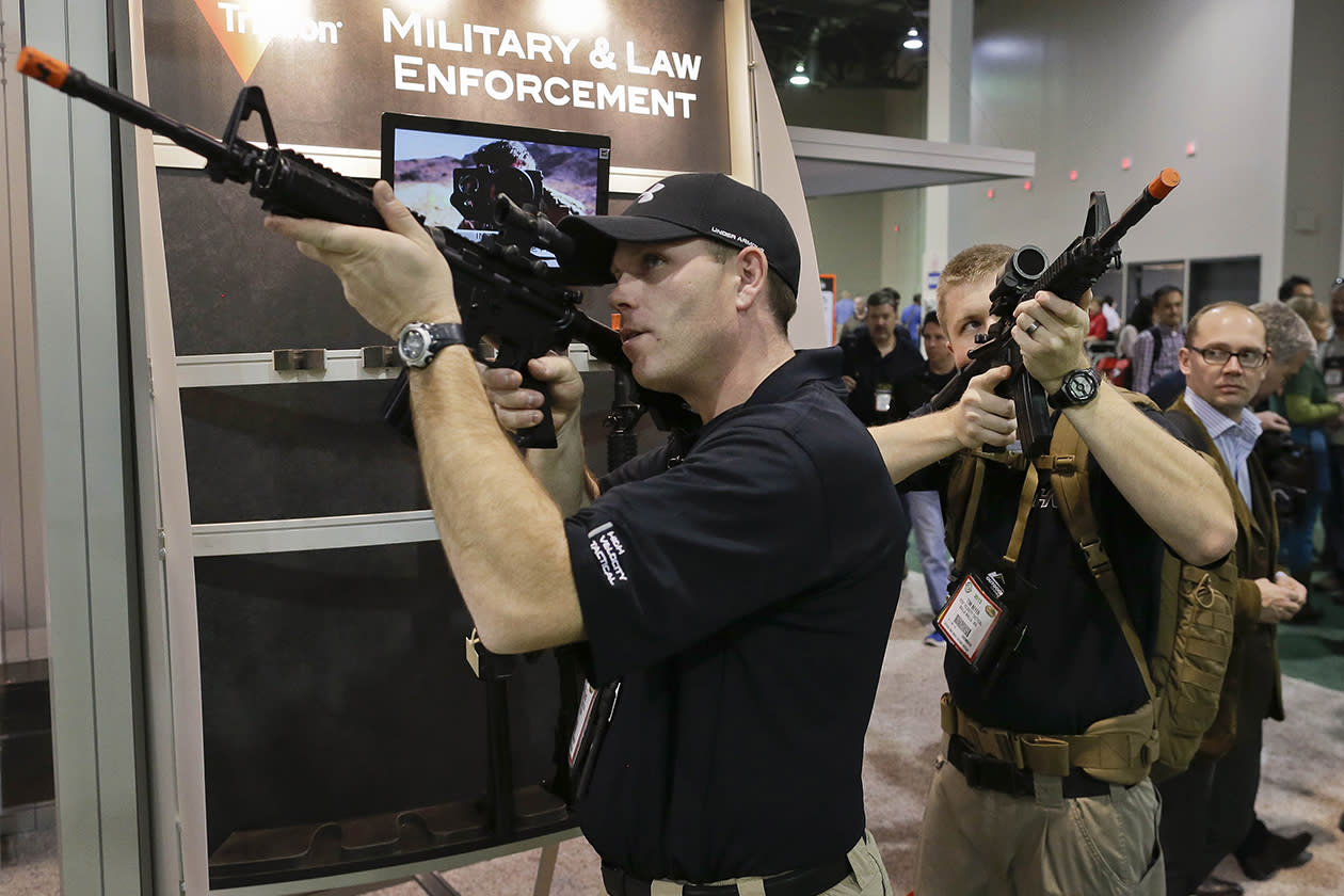 Brendan Vance, left, and Tom Beyer, co-owners of a tactical equipment and clothing store in Walla Walla, Wash., look through various rifle scopes.