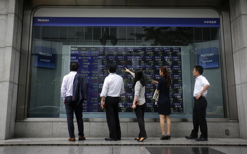 Pedestrians stand in front of a stock quotation board displaying various stock prices outside a brokerage in Tokyo
