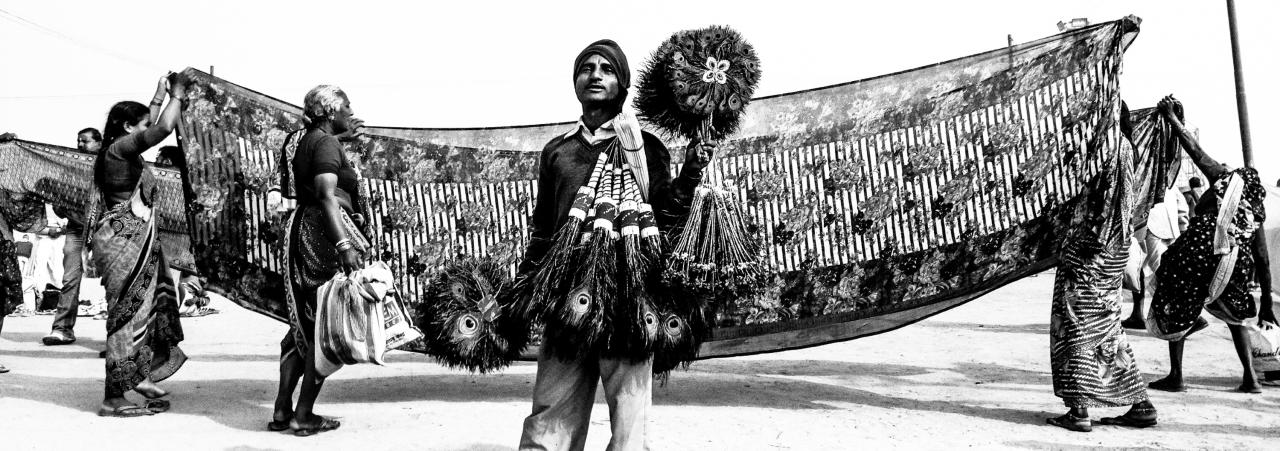 ALLAHABAD, INDIA - JANUARY 13: (EDITORS NOTE: Image was created using the iPhone panoramic application) A man sells peacock feathers as Hindu devotee hold out sarees to dry after having bathed on the banks of Sangam on January 13, 2013 in Allahabad, India. The Maha Kumbh Mela, believed to be the largest religious gathering on earth is held every 12 years on the banks of Sangam, the confluence of the holy rivers Ganga, Yamuna and the mythical Saraswati. The Kumbh Mela alternates between the cities of Nasik, Allahabad, Ujjain and Haridwar every three years. The Maha Kumbh Mela celebrated at the holy site of Sangam in Allahabad, is the largest and holiest, celebrated over 55 days, it is expected to attract over 100 million people. (Photo by Daniel Berehulak/Getty Images)