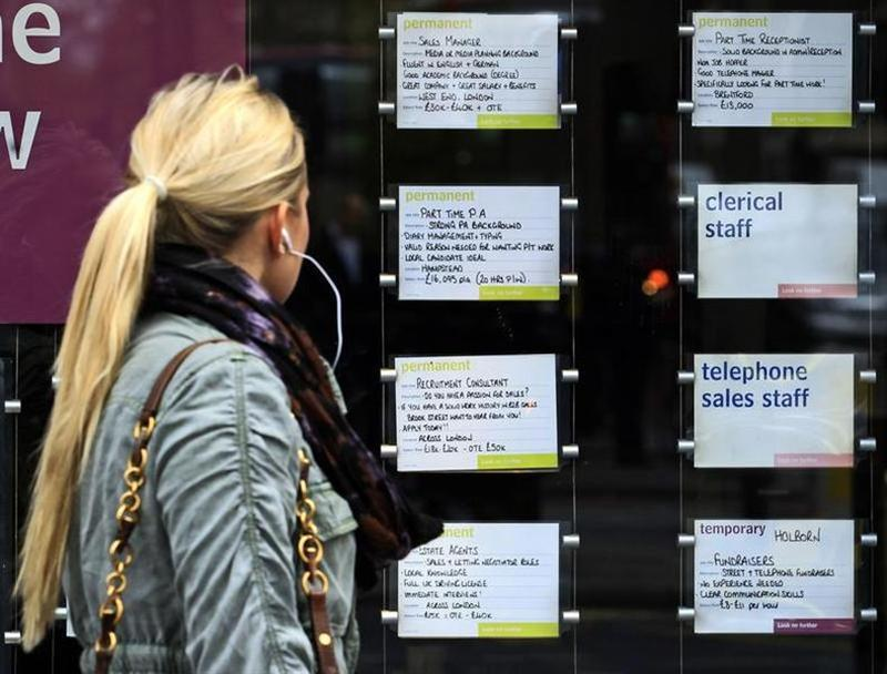 A woman passes notices for jobs in the window of a recruitment agency in London