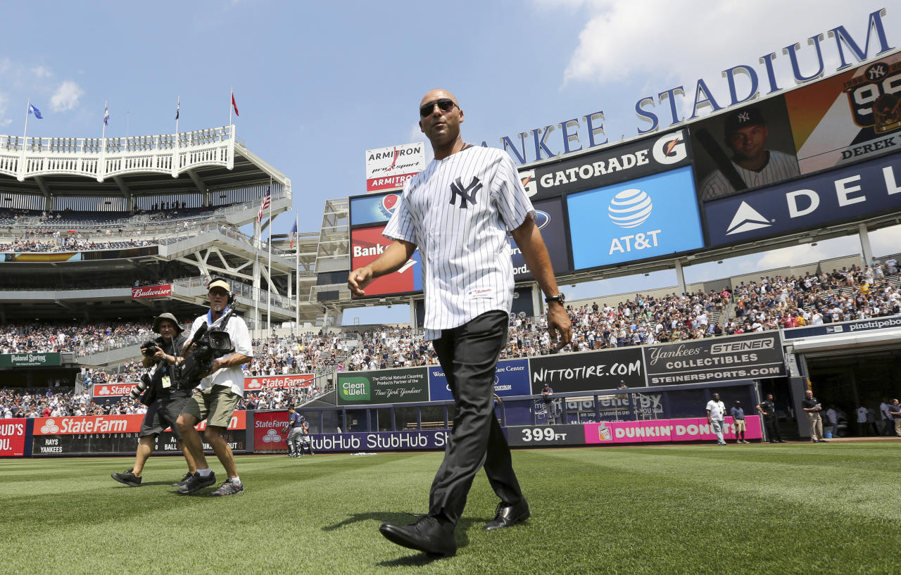 FILE - In this Aug. 13, 2016, file photo, former New York Yankees shortstop Derek Jeter walks onto the field as the 1996 Yankees baseball team were honored before the game against the Tampa Bay Rays at Yankee Stadium in New York. On Sunday, May 14, 2017, all eyes on the Bronx as the Yankees retire Derek Jeter's No. 2 jersey and unveil his plaque in Monument Park before their Mother's Day game against the Astros. (John Munson/The Star-Ledger via AP, Pool File)