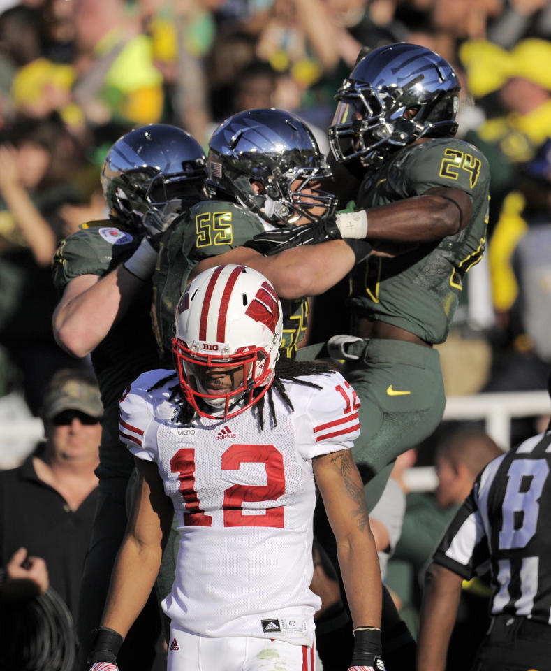 Oregon's Hroniss Grasu (55) celebrates with Kenjon Barner (24) after Barner scored a touchdown during the first half of the Rose Bowl NCAA college football game against Wisconsin, as Wisconsin's Dezmen Southward (12) walks away on Monday, Jan. 2, 2012, in Pasadena, Calif. (AP Photo/Mark J. Terrill)