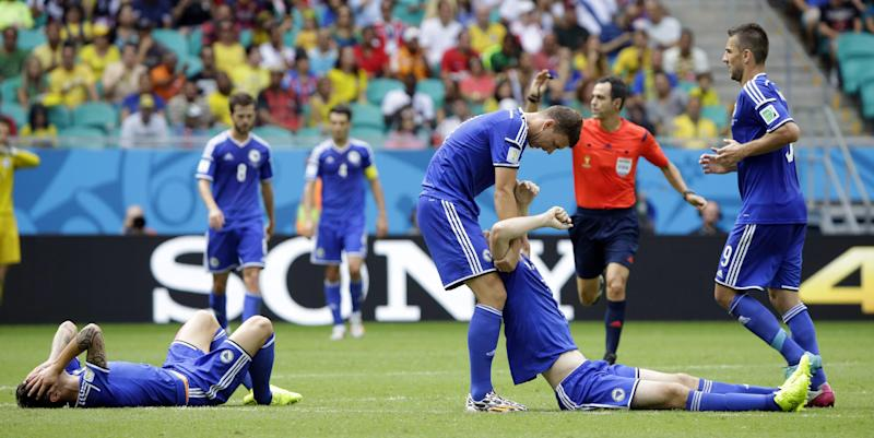 Bosnia's Muhamed Besic, left, and Bosnia's Toni Sunjic are assisted after crashing during the group F World Cup soccer match between Bosnia and Iran at the Arena Fonte Nova in Salvador, Brazil, Wednesday, June 25, 2014