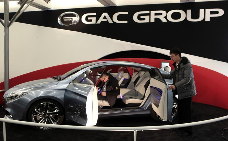 Two workers prepare GAC Motor's range-extended electric hybrid F-jet concept vehicle for display in Cobo Center in advance of media preview days of the North American International Auto show in Detroit