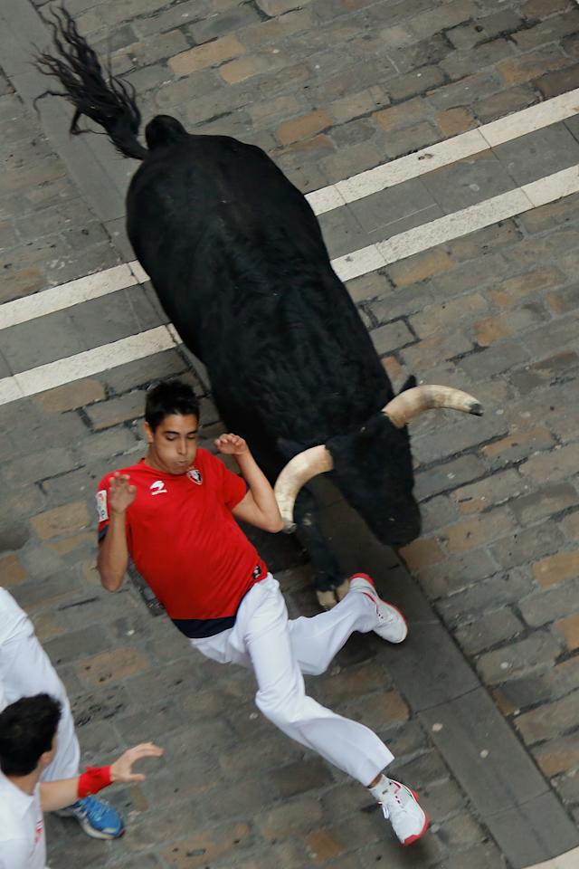 PAMPLONA, SPAIN - JULY 09: A reveller eludes a Valdefresno's ranch fighting bull's horn at Calle Estafeta during the fourth day of the San Fermin Running Of The Bulls festival, on July 9, 2013 in Pamplona, Spain. The annual Fiesta de San Fermin, made famous by the 1926 novel of US writer Ernest Hemmingway 'The Sun Also Rises', involves the running of the bulls through the historic heart of Pamplona, this year for nine days from July 6-14. (Photo by Pablo Blazquez Dominguez/Getty Images)
