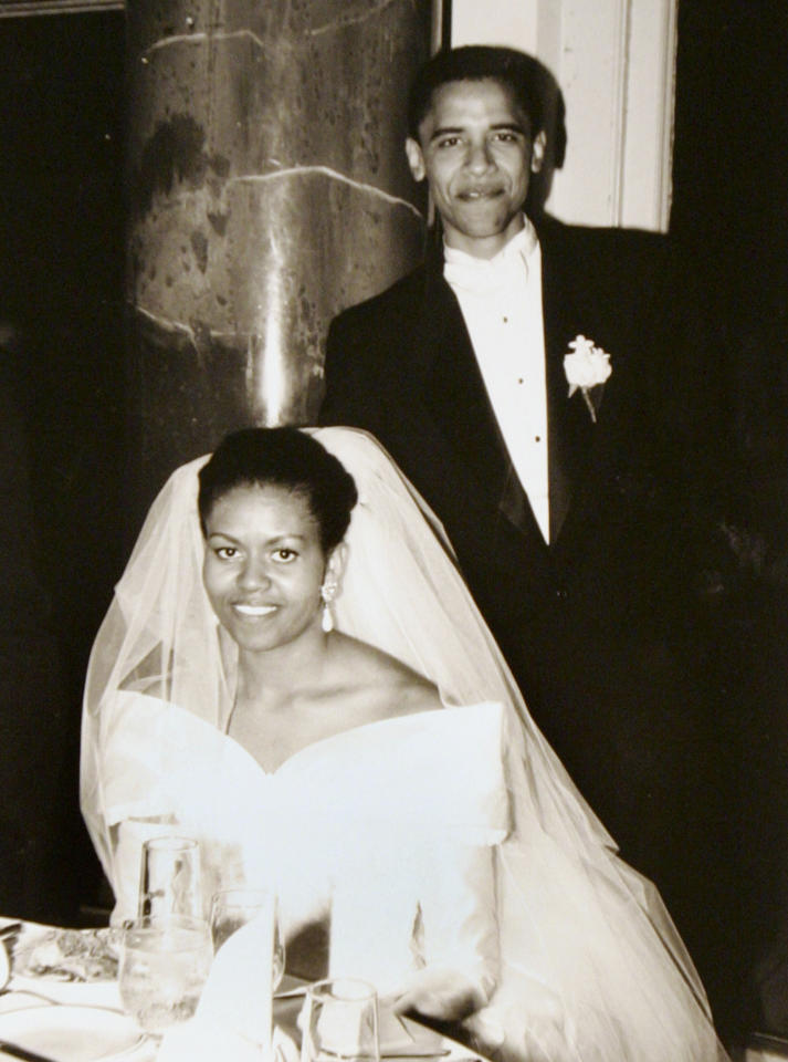 FILE- This Oct. 18, 1992 file photo released by Obama for America shows President Barack Obama and first lady Michelle Obama on their wedding day in Chicago. Obama's long-sleeve, portrait-collar wedding dress was one of her few fashion decisions that didn't move the needle. That was back in 1992, though. Her one-shoulder, white inaugural gown by Jason Wu, however, turned into a bona fide bridal-gown sensation, says Miller. It came at the right time, as designers continued to move away from all strapless all the time, she observes, and Obama wore it with the right happy, confident attitude that brides strive for.