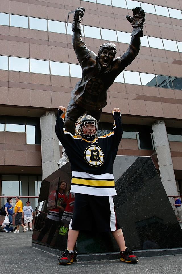 BOSTON, MA - JUNE 24: A young fan of the Boston Bruins poses in front of a statue of Bobby Orr prior to the Bruins hosting the Chicago Blackhawks in Game Six of the 2013 NHL Stanley Cup Final at TD Garden on June 24, 2013 in Boston, Massachusetts. (Photo by Jim Rogash/Getty Images)