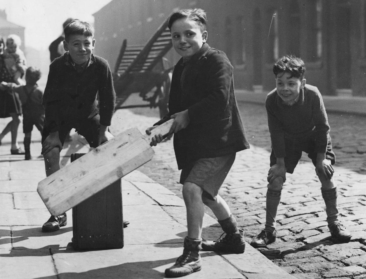 22nd April 1939:  City boys enjoying a game of street cricket with a large home-made bat and a suitcase as the wicket.  (Photo by Fox Photos/Getty Images)