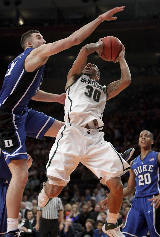 Duke forward Miles Plumlee (21) tries to prevent a shot by Michigan State guard Brandon Wood (30) in the first half of an NCAA college basketball game at Madison Square Garden in New York, Tuesday, Nov. 15, 2011. (AP Photo/Kathy Willens)