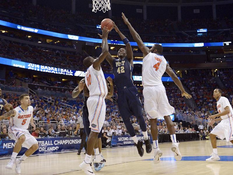 Pittsburgh forward Talib Zanna (42) shoots as Florida center Patric Young (4) and forward Dorian Finney-Smith (10) defend during the second half in a third-round game in the NCAA college basketball tournament  Saturday, March 22, 2014, in Orlando, Fla