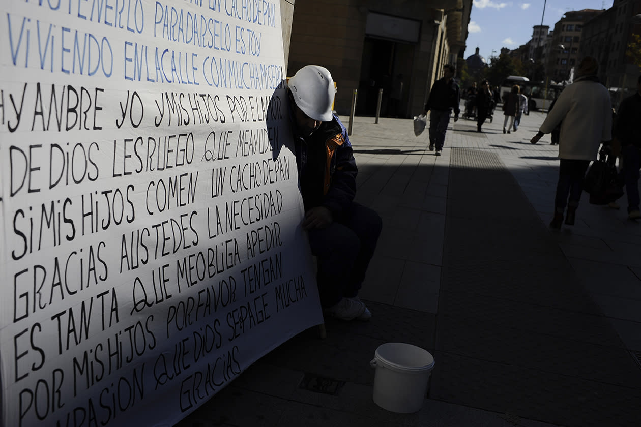 A man begs for alms next a giant banner with a description about his critical economic situation on one street, in Pamplona, northern Spain.