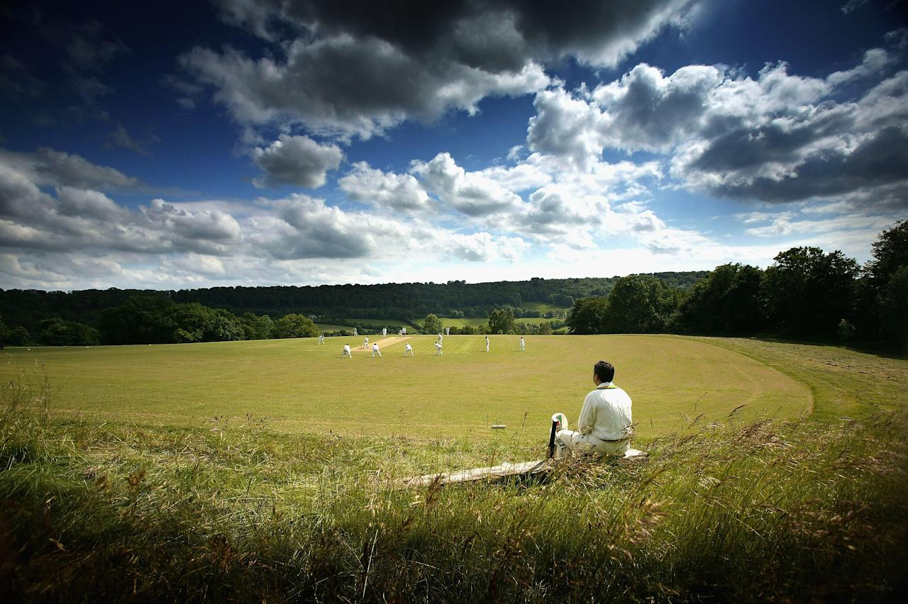 SHEEPSCOMBE, ENGLAND - JUNE 14: (EDITORS NOTE: A polarizing filter was used for this image.) A Cricketer waits for his turn to bat at Sheepscombe Cricket Club on June 14, 2005 in Sheepscombe, England.  (Photo by Laurence Griffiths/Getty Images)