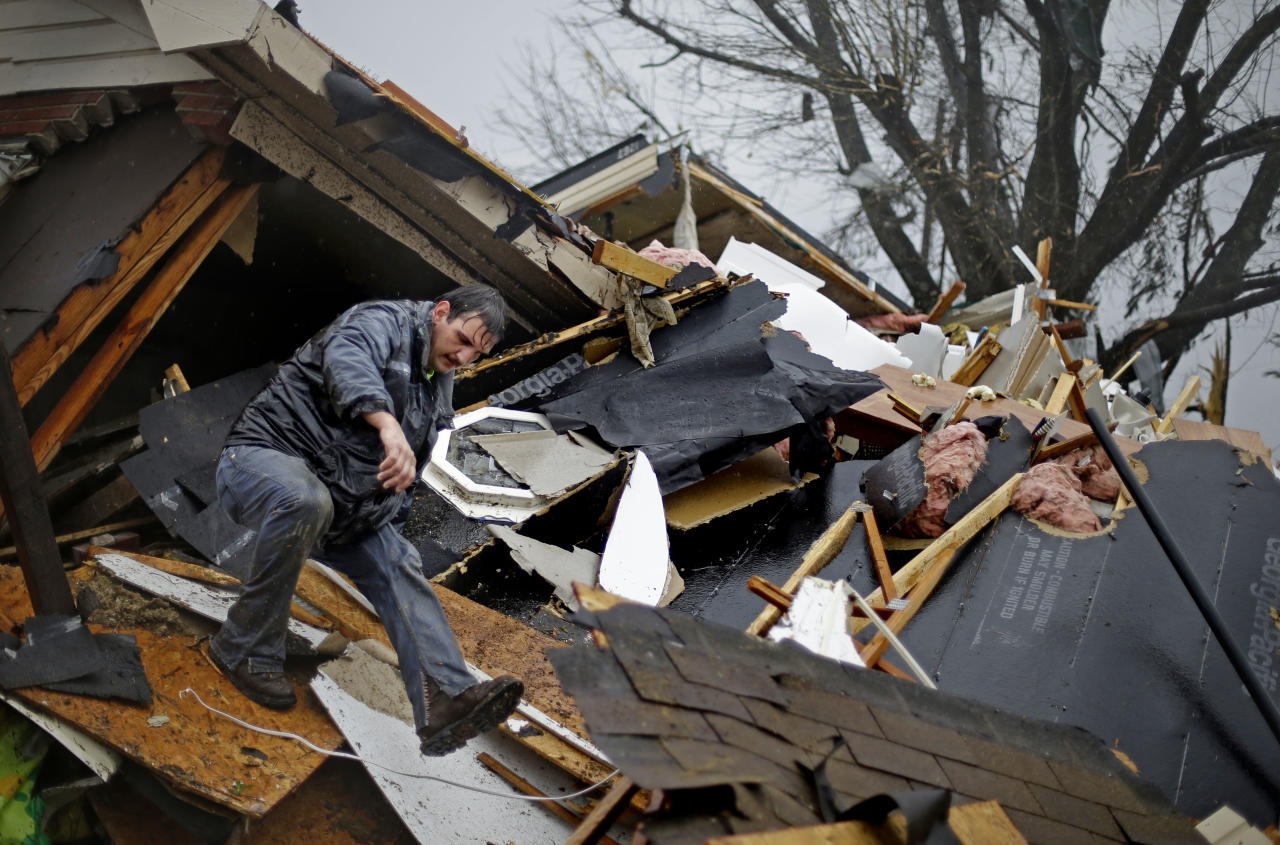 Nathan Varnes, of Cartersville, Ga., helps search a destroyed home for a dog after a tornado struck, Wednesday, Jan. 30, 2013, in Adairsville, Ga. A fierce storm system that roared across Georgia has left at least one person dead after it demolished buildings and flipped vehicles on Interstate 75 northwest of Atlanta. (AP Photo/David Goldman)