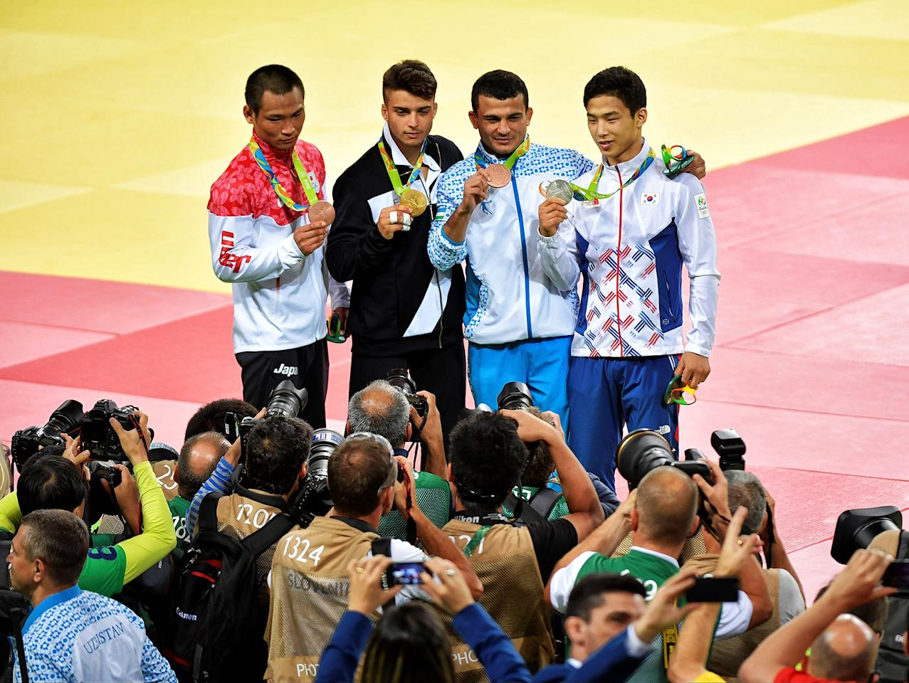 <p>Under 66kg medallists L-R: Bronze; Masashi Ebinuma of Japan, Gold; Fabio Basile of Italy, Bronze; Rishod Sobirov of Uzbekistan and Silver; Ba-Ul An of South Korea pose in front of the photographers during the medal ceremony on day 2 of the 2016 Rio Olympic Judo on Sunday, August 7 held at the Carloca Arenas, Barra, Rio de Janeiro, Brazil. (David Finch/Getty Images) </p>