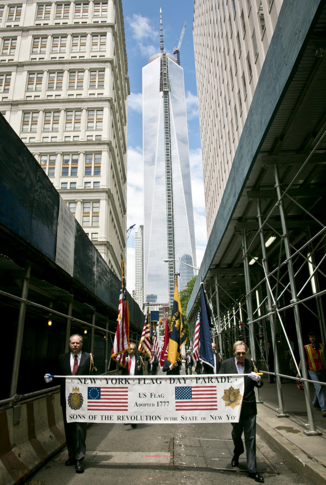 With the new WorldTrade Center tower as a backdrop, a Flag Day procession moves along Fulton Street on Friday, June 14, 2013 in New York. (AP Photo/Bebeto Matthews)