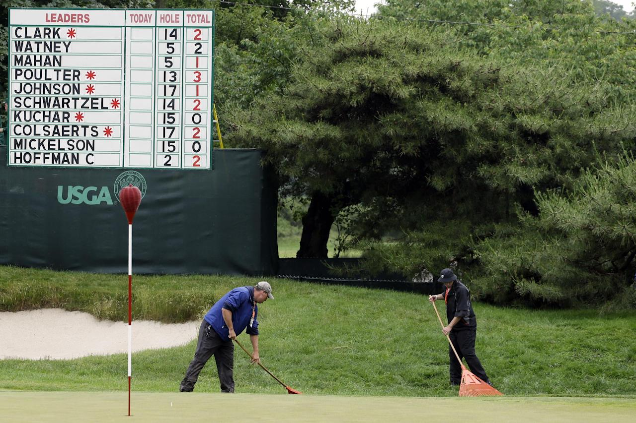 Course workers rake the first green after a weather delay in the first round of the U.S. Open golf tournament at Merion Golf Club, Thursday, June 13, 2013, in Ardmore, Pa. (AP Photo/Darron Cummings)